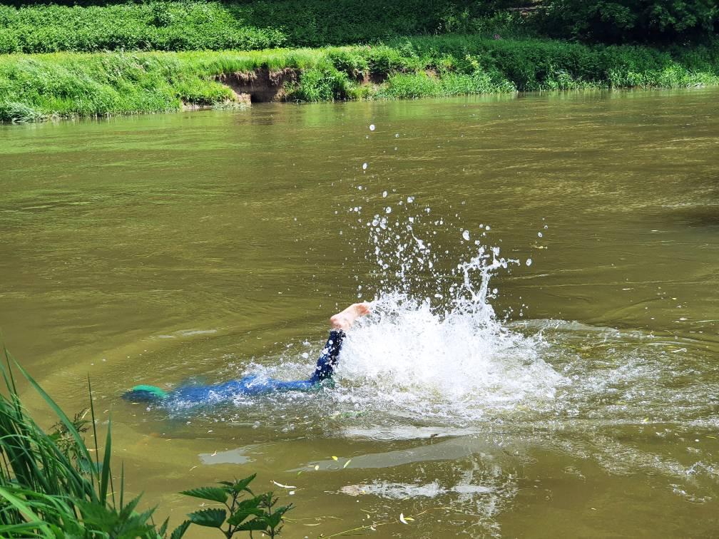 Ein Kind mit Neoprenanzug schwimmt in der Donau